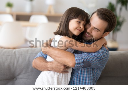 Adorable preschool daughter wearing white dress hugging loving father looking at him with love and tenderness. Multi-ethnic diverse friendly family on couch at modern home spending free time together