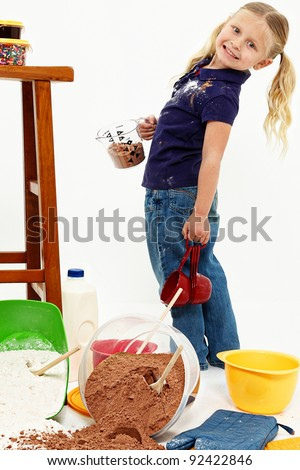 Adorable preschool girl child standing on floor covered in baking mess over white.