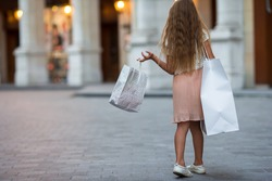 Adorable preschool girl walking with shopping bags in Paris outdoors