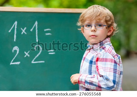 Adorable preschool kid boy with glasses at blackboard practicing mathematics, outdoor. school or nursery. Back to school concept