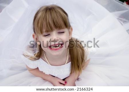 Adorable preschooler dressed up as a bride. - stock photo