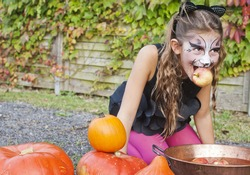 Adorable, pretty, young girl dressed as a black cat, apple bobbing for Halloween