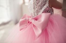 adorable puffy pink dress for a girl from tulle, with a huge pink bow on the back, shiny silver sequin back