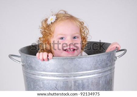 adorable red haired girl hiding in a bin