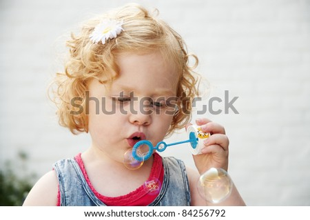 adorable redhead blowing a bubble - stock photo