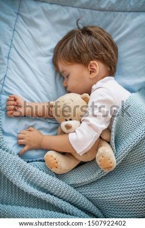 Adorable redhead toddler baby sleeping with plush toy in sofa. Morning slumber. Baby toddler asleep with teddy bear. Little sweet toddler boy sleeping in his bed
