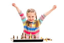 Adorable school age girl feels extremely happy about winning in chess isolated on a white background