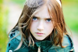 Adorable school aged angry girl portrait outdoor