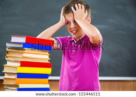 Adorable schoolboy with stack of books in classroom