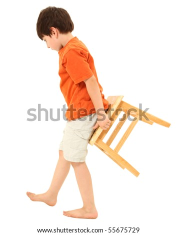 Adorable seven year old boy carrying a stool behind him.