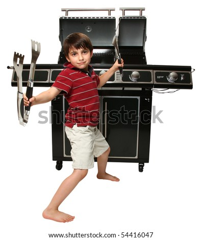 Adorable seven year old boy with grill utensils in front of large gas grill.