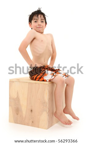 Adorable seven year old french american boy in swim suit and wet hair. Ribs showing skinny thin.