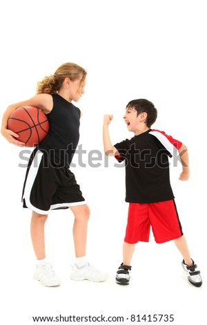 Adorable short boy child shaking fist at taller girl basketball player over white.