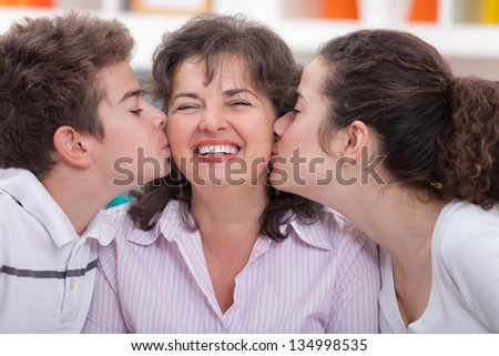 Adorable siblings kissing their mother
