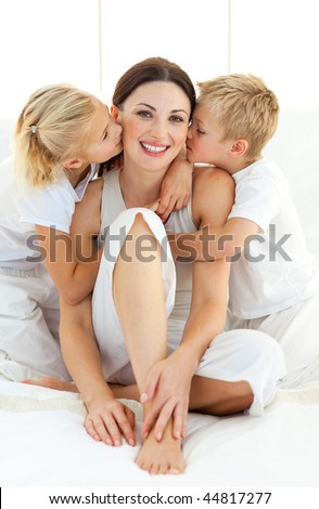 Adorable siblings kissing their mother sitting on a bed at home