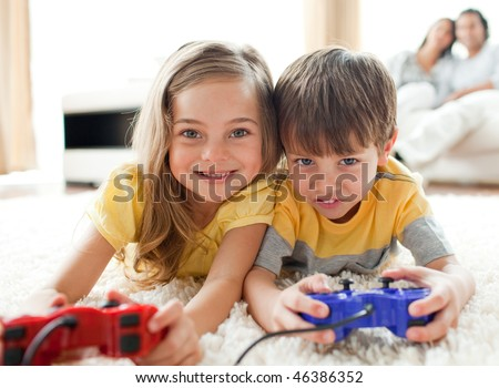 Adorable siblings playing video game in the living room