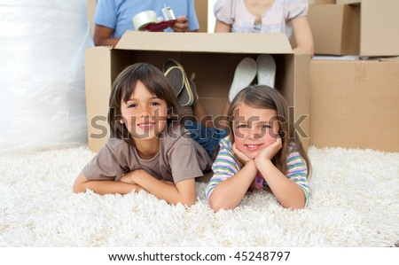 Adorable siblings playing with boxes while moving house