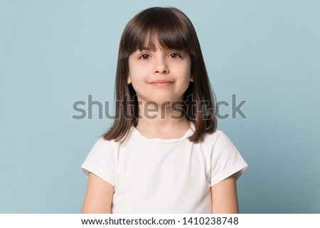 Adorable six years old girl in white t-shirt isolated on blue studio background, pretty brown-haired fringe hairstyle european appearance child pose indoor smiling look at camera, generation Z concept