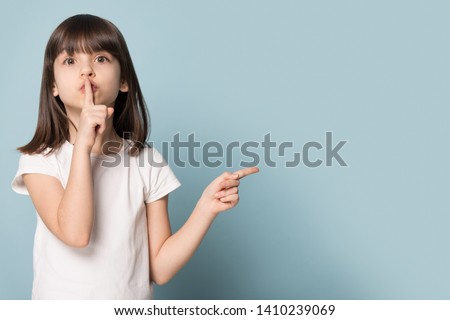 Adorable six years old little girl holding finger on lips symbol of hush gesture of asking to be quiet. Silence or secret concept image isolated on blue studio background with copy free space for text
