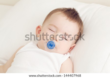 Adorable sleeping baby on the pillow with pacifier