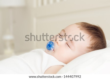 Adorable sleeping baby on the pillow with pacifier and bottle of milk at the background