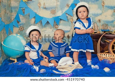 Adorable small children in a suit of the seaman smiling and having fun in studio. Sea style. Dreams of the ship, adventures and travel. Portrait of funny lovely little baby