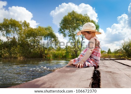 Adorable small girl sitting on the wooden bridge and dangling her legs in the water