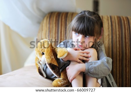 Adorable small girl with dark hair in grey dress hugs her bunny