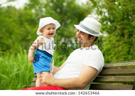 Adorable smiling baby boy with father in the park