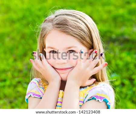 Adorable smiling blond little girl with long hair and many-colored manicure