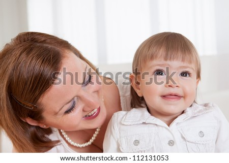 Adorable smiling little blonde girl with her doting mother posing for the camera