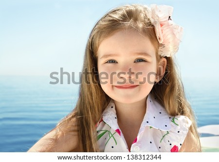 Adorable smiling little girl on beach vacation