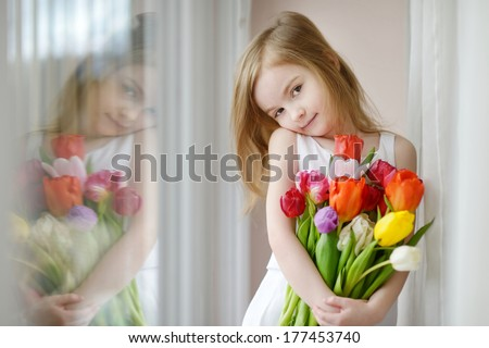 Adorable smiling little girl with tulips by the window