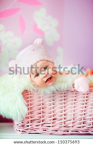 adorable smiling newborn baby girl in pink knitted bear hat lies at basket