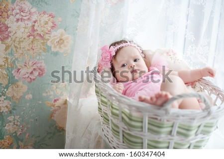 adorable smiling newborn baby girl lies at basket with flowers