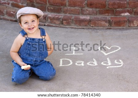 """adorable smiling toddler writing """"I love Daddy in sidewalk chalk"""
