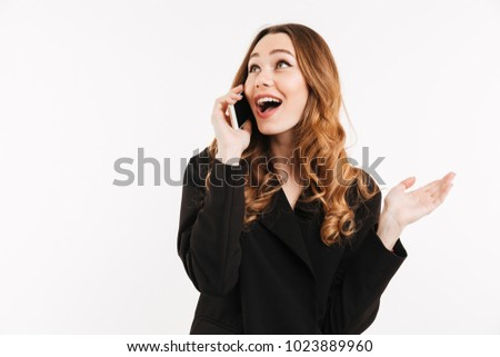 Adorable smiling woman with trendy hairstyle in black jacket talking on mobile phone and having pleasant conversation isolated over white background