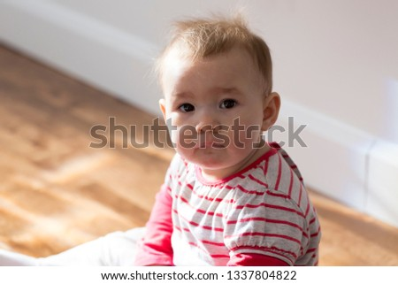 Adorable solemn looking fair baby girl sitting on floor drooling and looking up with dark eyes
