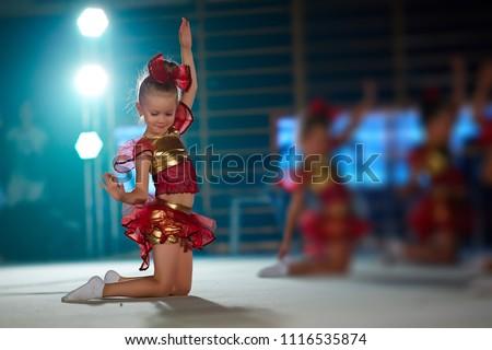 Adorable sporty little girl in rhythmic gymnastics