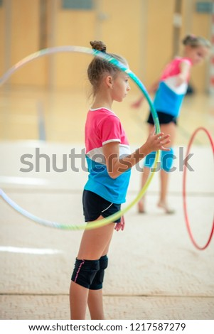 Adorable sporty little girl in rhythmic gymnastics with hoop