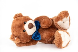 Adorable stuffed toy with blue ribbon bow on neck. Plush bear laying isolated, calm and relaxed. Plaything for children, present for holidays, gift for Valentines day. Cuddly and soft doll for playing