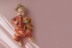 Adorable stylish baby smiling and hugging  toy bear against pink background. Cute infant in pajama with knitted toy