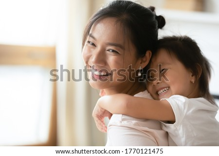 Adorable sweet little preschool kid daughter cuddling from back smiling beautiful vietnamese mother, enjoying sweet tender family moment together indoors, having fun at home, head shot close up.