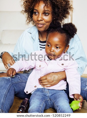 adorable sweet young afro-american mother with cute little daughter, hanging at home, having fun playing smiling, lifestyle people concept #520852249
