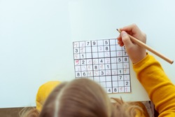 Adorable teen girl solving sudoku at desk at school or at home. View from above