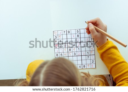 Adorable teen girl solving sudoku at desk at school or at home. View from above Foto stock ©
