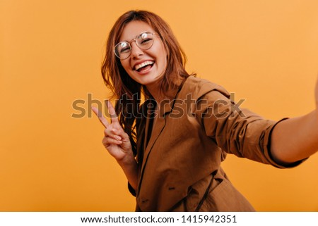 Adorable teen with snow-white smile makes selfie on orange background. Indoors portrait of dark blond lady in stylish glasses tingling peace sign #1415942351