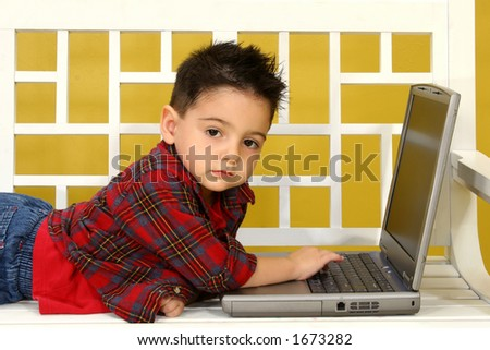 Adorable three year old boy with laptop.