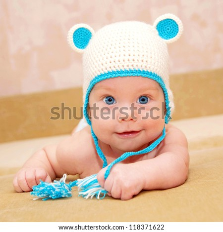 Adorable tiny smiling baby with blue eyes lying on the sofa. Selective focus on the child's face. Kid wearing a funny knit handmade cap with ears