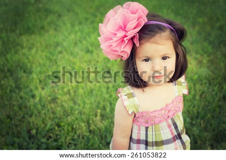 Adorable toddle girl with big pink bow headband and cute romantic pink and green dress smiling looking at camera against green grass background. Horizontal, retouched, filter, copy space.